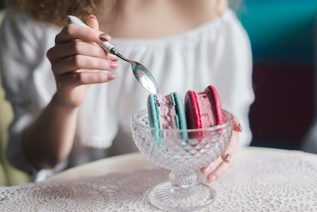 スプーンでおいしい冷凍アイスクリームデザートを食べる女のクローズアップ