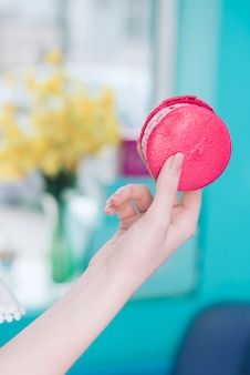 ぼやけて背景に対してピンクの冷凍アイスクリームサンドイッチを持つ女性の手のクローズアップ