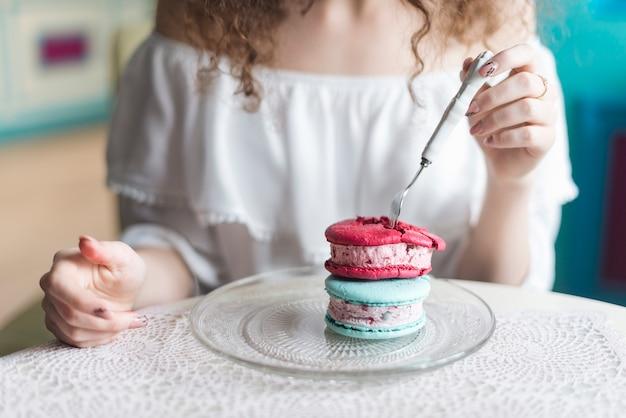アイスクリームサンドイッチを食べる女の中央部