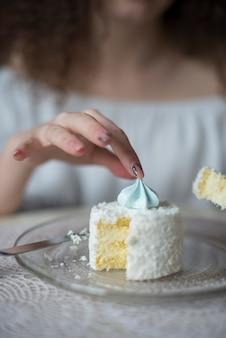 皿の上のケーキの上のメレンゲを拾う女性のクローズアップ