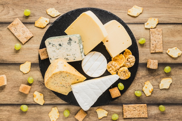 木製の机の上の丸いスレートのブドウ、クラッカー、カリカリのパン、チーズブロック