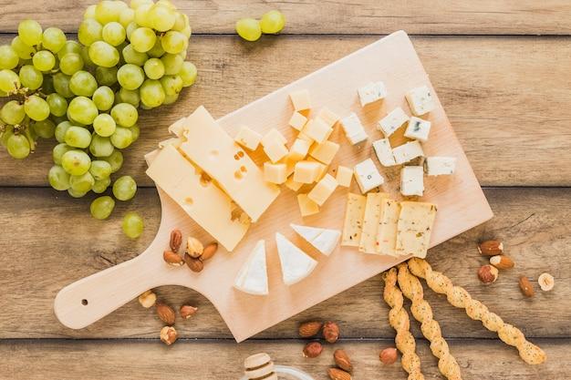 木製の机の上のまな板の上の緑のブドウ、アーモンド、パンの棒およびチーズブロック