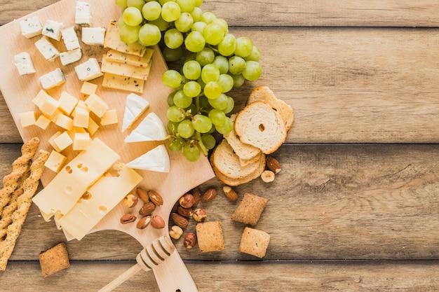 パン棒、チーズブロック、ブドウ、パン、クッキー、木製の机の上