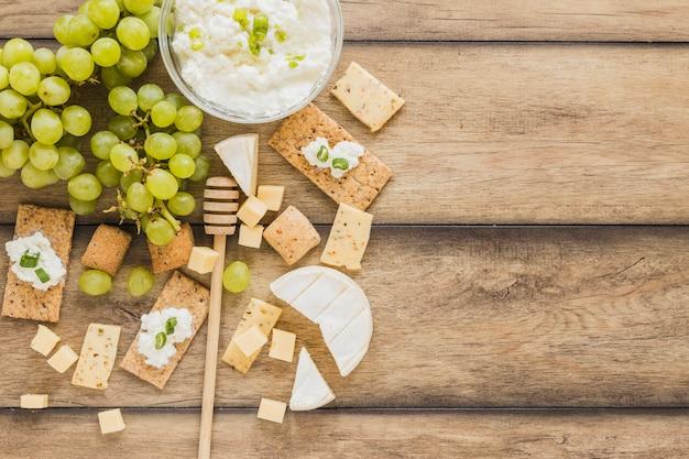 チーズクリームボウル、ブドウ、クラッカー、チーズブロック、木製の机の上の蜂蜜ディッパー