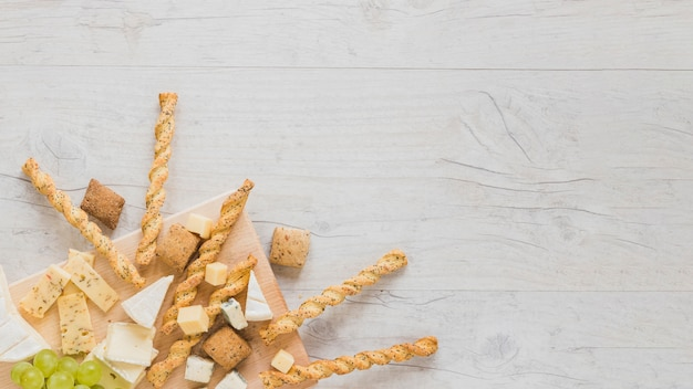 クッキー、パンの棒、チーズブロック、木の表面の隅にぶどう