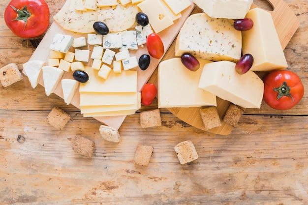 木製の机の上の赤いトマト、ブドウ、オリーブ、チーズブロック