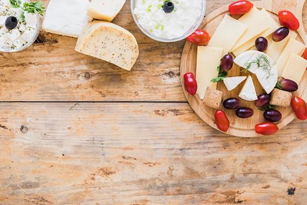 チーズディップと木製の机の上のブドウとトマトのブロック