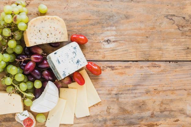 ブルーチーズブロックと木製の机の上のブドウとトマトのスライス