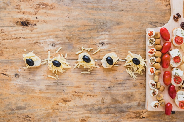 粉チーズとブラックオリーブの木製の机の上のミニサンドイッチ