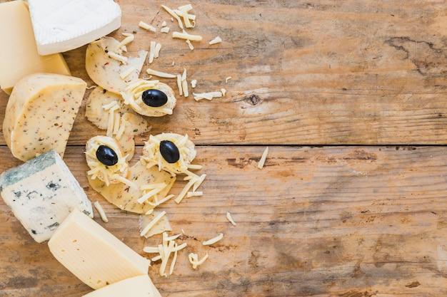 木製の机の上のミニサンドイッチとチーズの盛り合わせ