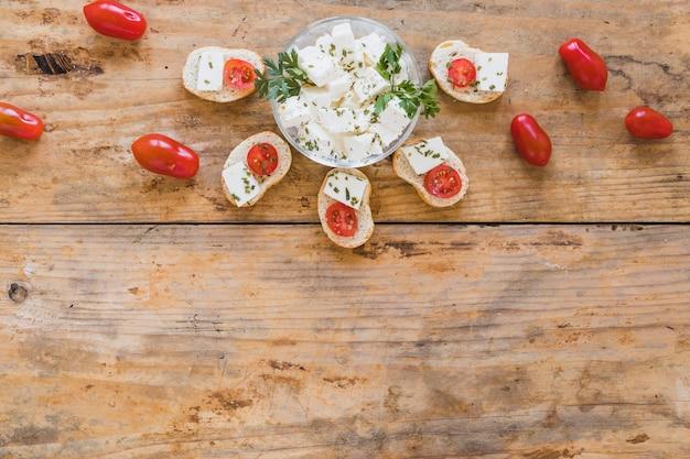 チーズとトマトの木製の机の上のミニサンドイッチ