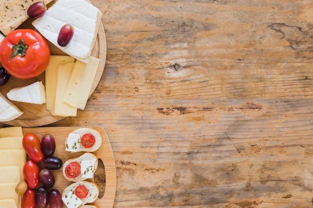 チーズブロックと木製の机の上のトマトのミニサンドイッチ