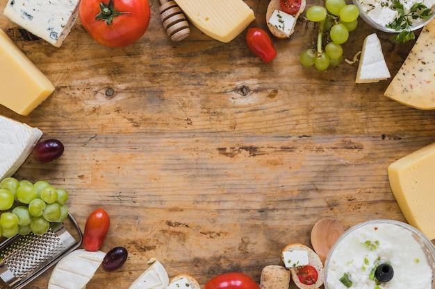 トマト、ブドウ、ミニサンドイッチ、木製の机の上のテキストを書くためのスペースとチーズの盛り合わせ
