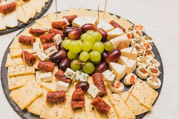 Вид сверху на копченые колбаски, сырное ассорти и виноград на грифельной тарелке
