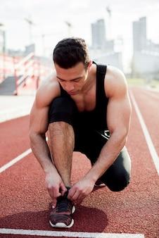 Портрет молодого человека фитнеса связывая шнурок на поле легкой атлетики