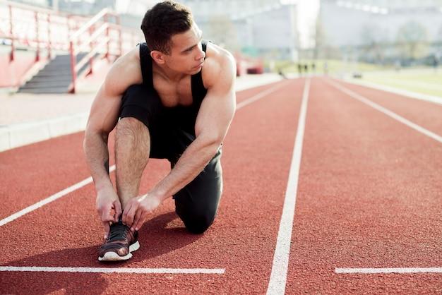 Спортсмен-спринтер готовится к бегу, завязывая шнурки на беговых дорожках стадиона