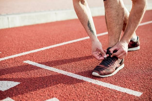 Низкая часть спортсмена мужского пола на линии старта, связывающей его шнурок на беговой дорожке
