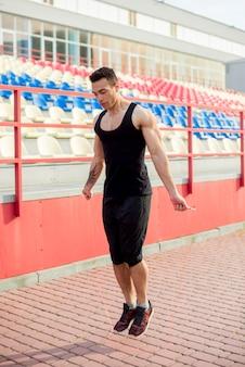 スタジアムのアリーナの前でスキップする筋肉のオスの運動選手