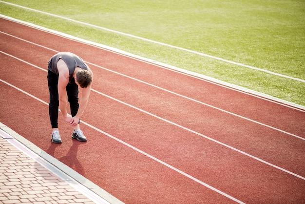 Молодой мужчина спортсмен, стоя на гоночной трассе, протягивая ее руки