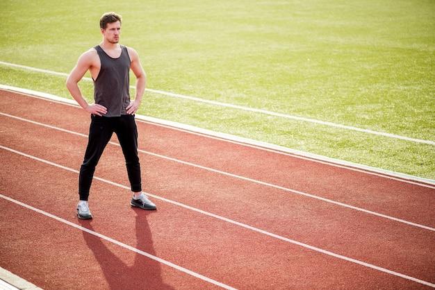Портрет уверенно спортивного человека, стоящего на гоночной трассе