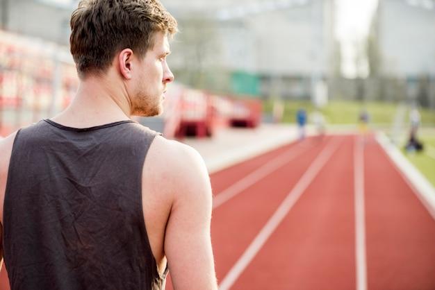 Вид сзади мужской бегун, стоя на гоночной трассе, глядя