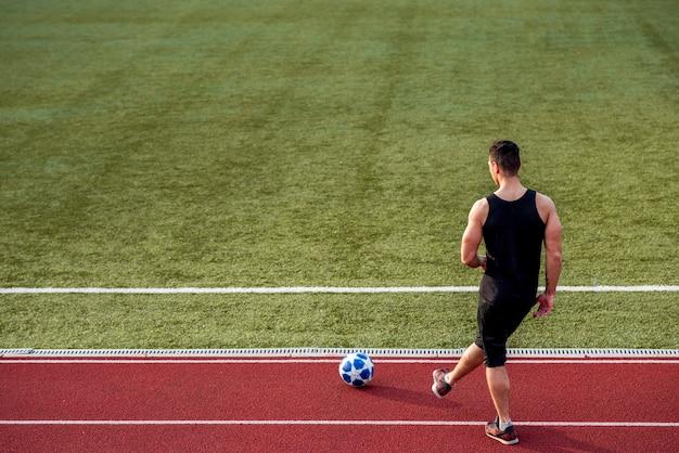 サッカーボールとレーストラックで遊んでスポーツマンの背面図