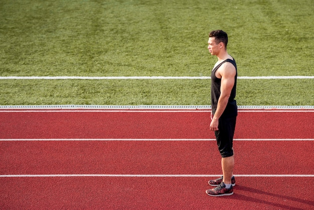 赤いランニングトラックの上に立ってフィットネス若い男性ランナー