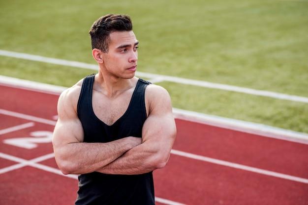 彼の腕を持つ筋肉の若いスポーツ人がレーストラックに立っています。