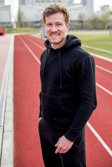 Улыбающийся портрет мужчины спортсмена, стоящего на гоночной трассе