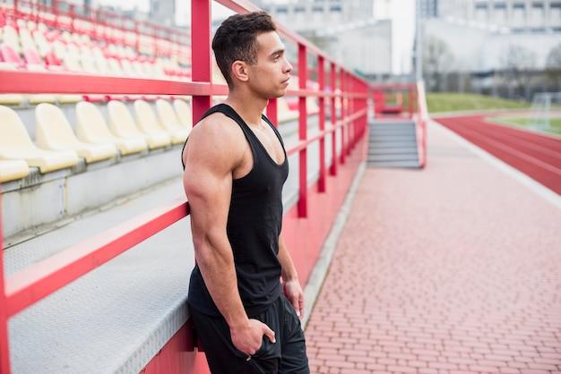 Взгляд со стороны мужского спортсмена стоя близко отбеливатель смотря прочь