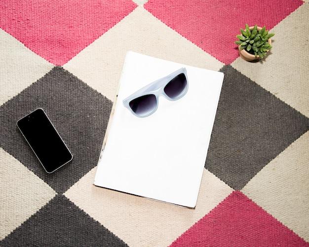 携帯電話と眼鏡のオフィスのデスクトップ