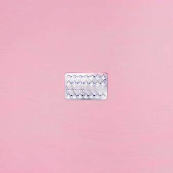Таблетки сверху на розовом фоне