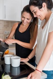 同性カップルのキッチンでコーヒーを注ぐ