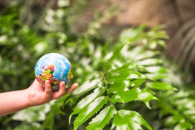植物の前に地球のボールを持っている子供の手のクローズアップ