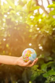 日光の下で緑の植物の前に地球のボールを持っている子供の手のクローズアップ