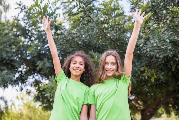 Портрет улыбающейся девушки, поднимая руку, стоя перед деревьями