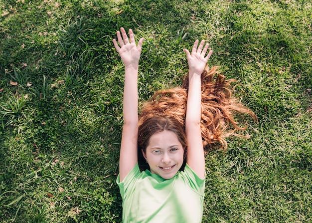 日光の下で草の上に横たわる陽気な女の子