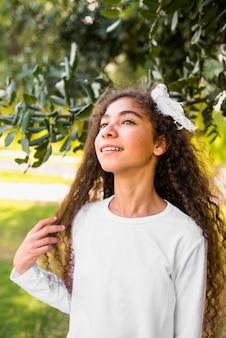 公園に立っている微笑の女の子のクローズアップ