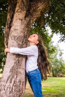 木を抱き締める長い毛を持つ少女の低角度のビュー