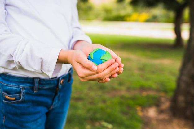 カップ状の手で地球を保持している女の子の中央部