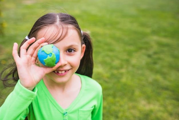 粘土の世界を手で保持しているきれいな女の子のクローズアップ