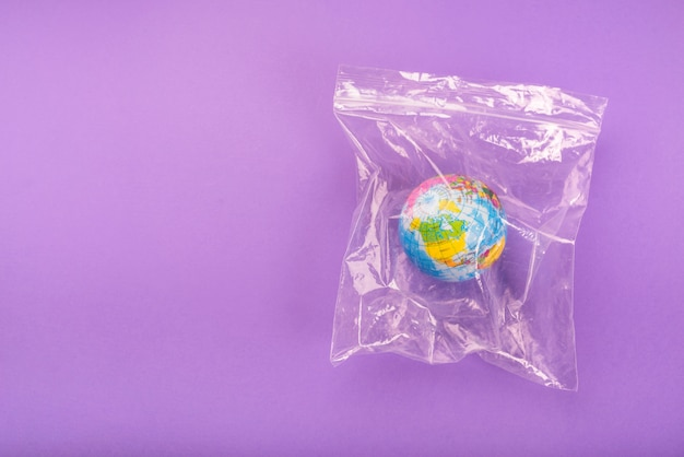 Вид сверху на глобус в пластиковом пакете на молнии на фиолетовом фоне