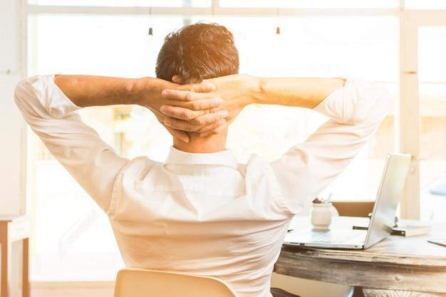 頭の上の彼の手で椅子に座っている実業家の背面図