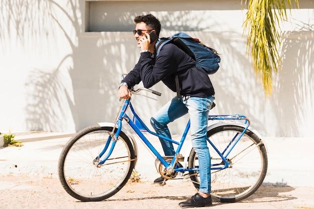 スマートフォンで話している青い自転車の上に座って彼のバックパックを持つ男の肖像
