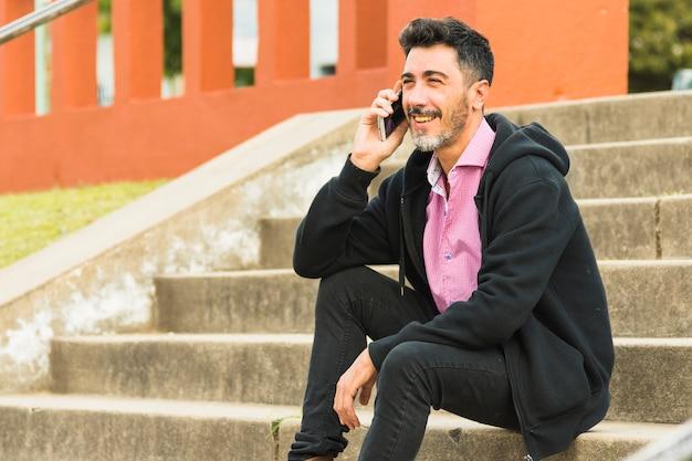 携帯電話で話している階段に座っているスタイリッシュな現代人