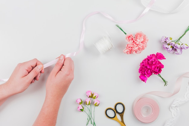 白い背景の上のリボンと花の花束を作る女性の手のクローズアップ