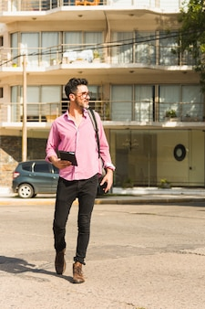 彼のバックパックが付いている通りを歩いて手に日記を持って男の肖像