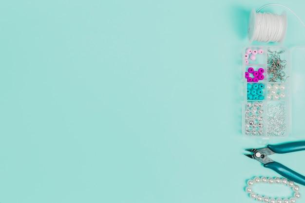 スレッドスプール真珠ケース。ペンチとテキストを書くためのコピースペースを持つティール背景にブレスレット