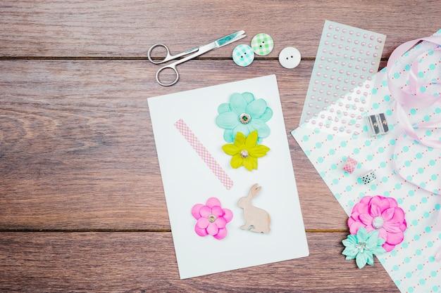 花でグリーティングカードを作ります。ボタンリボンと木製のテーブルの上のビーズ