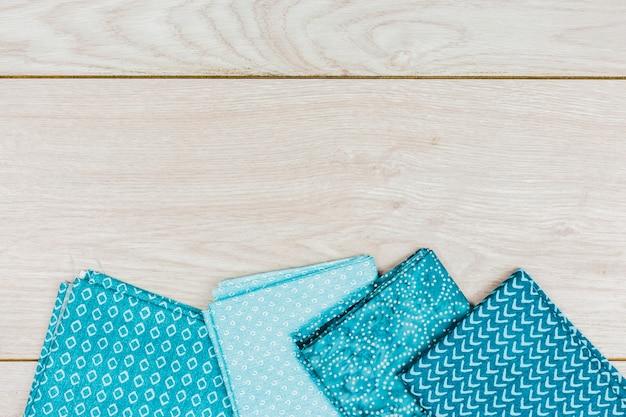 木製の机の上の異なるプリントと折られた青い服の高架ビュー